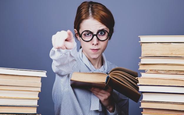 Młody nauczyciel w okularach z książkami.