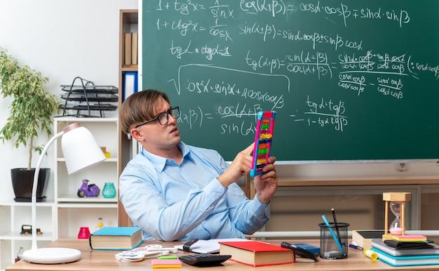 Młody nauczyciel w okularach z rachunkami patrząc zdezorientowany przygotowując lekcję, siedząc przy ławce szkolnej z książkami i notatkami przed tablicą w klasie
