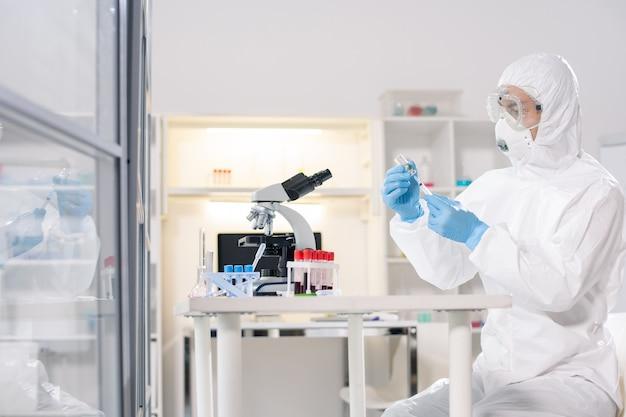 Młody naukowiec lub farmaceuta w ochronnej odzieży roboczej siedzi w laboratorium i pracuje nad stworzeniem nowej szczepionki