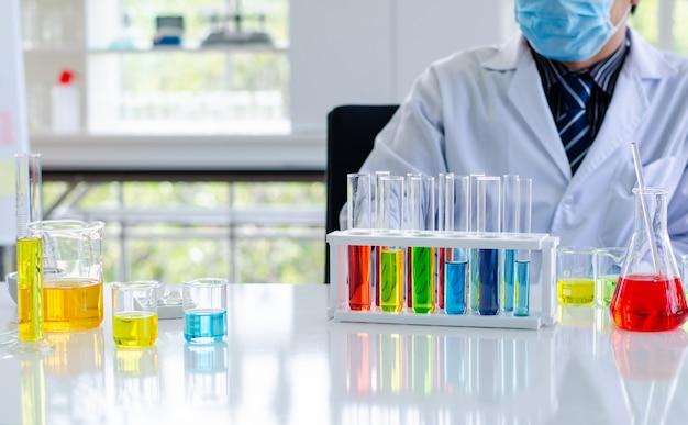 Młody naukowiec patrząc przez mikroskop w laboratorium. młody naukowiec robi jakieś badania.