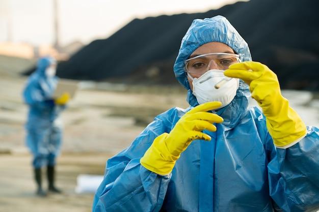 Młody naukowiec w ochronnej odzieży roboczej, patrzący na próbkę toksycznej gleby w kolbie podczas prowadzenia badań ekologicznych z kolegą