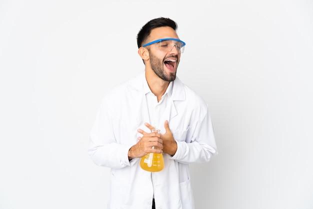 Młody naukowy człowiek na białym tle na białej ścianie, dużo uśmiechając się
