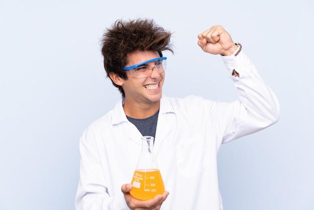 Młody naukowy mężczyzna nad odosobnioną błękit ścianą świętuje zwycięstwo