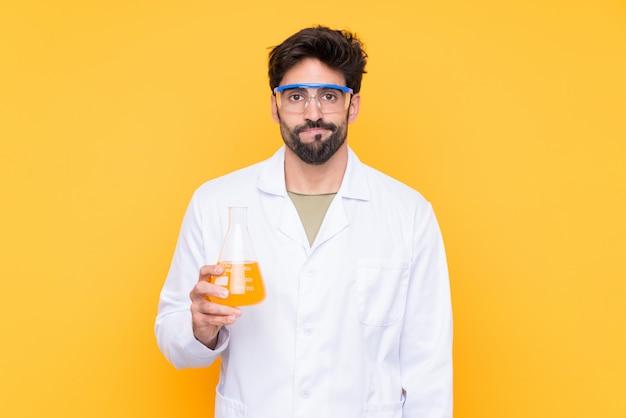 Młody naukowy mężczyzna nad odosobnioną kolor żółty ścianą z smutnym wyrażeniem