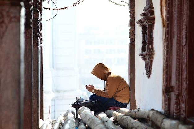 Młody nepalczyk koncentruje się na swoim telefonie na ulicy