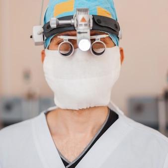 Młody neurochirurg w masce medycznej z profesjonalnymi lupami z lupami binarnymi do mikrochirurgii. instrumenty chirurgiczne