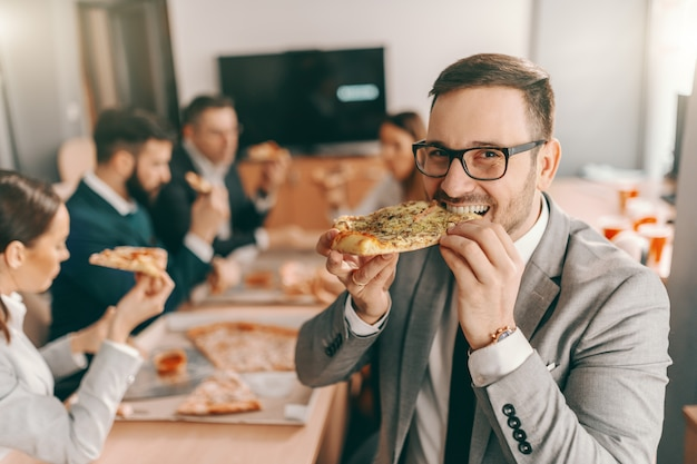 Młody nieogolony biznesmen w wizytowym i okularach, jedzenie pizzy na obiad. w tle koledzy też jedzą obiad.