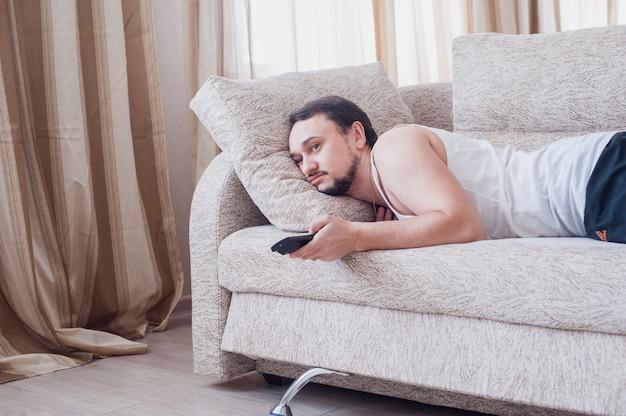 Młody nieogolony facet leniwie odpoczywa w dresie