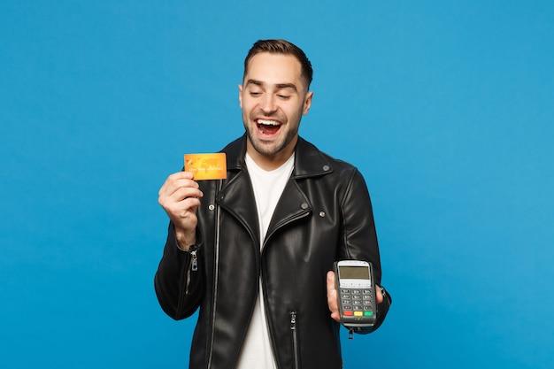 Młody nieogolony mężczyzna czarna kurtka biała koszulka trzymać w ręku bezprzewodowy terminal płatniczy nowoczesny bank do przetwarzania i nabywania płatności kartą kredytową na białym tle na tle niebieskiej ściany. koncepcja życia ludzi.