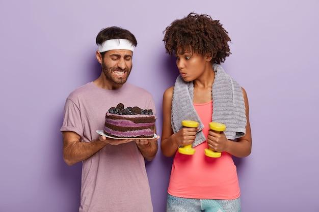 Młody nieogolony mężczyzna trzyma talerz ciasta, zaciska zęby, ma ochotę zjeść deser, a zaskoczona kręcona kobieta trenuje mięśnie brzucha z hantlami