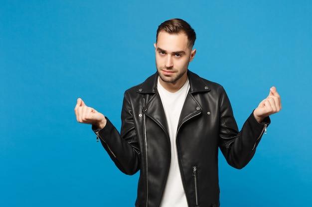 Młody nieogolony mężczyzna w czarnej kurtce biały t-shirt pocierając palce, pokazując gest gotówki, prosząc o pieniądze na białym tle na tle niebieskiej ściany portret studio. koncepcja życia ludzi. makieta miejsca na kopię.