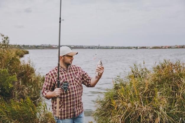 Młody nieogolony mężczyzna w kraciastej koszuli, czapce i okularach przeciwsłonecznych wyciągnął wędkę i trzyma złowioną rybę na brzegu jeziora w pobliżu krzewów i trzcin. styl życia, rekreacja, koncepcja wypoczynku rybaka