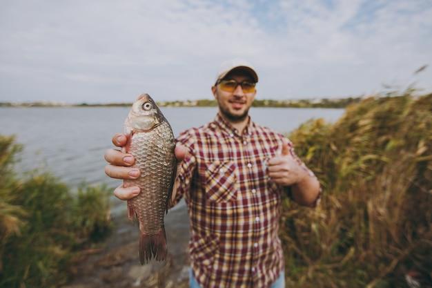 Młody nieogolony mężczyzna w kraciastej koszuli, czapce i okularach przeciwsłonecznych złowił rybę, pokazuje ją i gestykuluje kciukami na brzegu jeziora na tle wody i trzcin. styl życia, rekreacja, koncepcja wypoczynku.