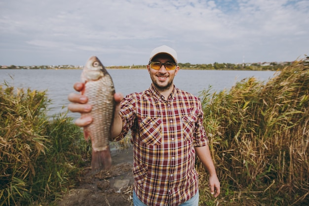 Młody nieogolony mężczyzna w kraciastej koszuli, czapce i okularach przeciwsłonecznych złowił rybę, pokazuje ją i uśmiecha się na brzegu jeziora na tle wody, krzewów i trzcin. styl życia, rekreacja rybaka, koncepcja wypoczynku