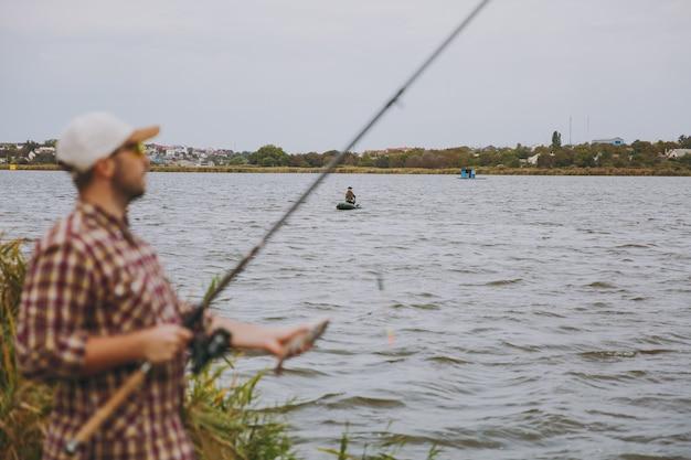Młody nieogolony mężczyzna w kraciastej koszuli, czapce, okularach przeciwsłonecznych wyciągnął wędkę i trzyma złowioną rybę na brzegu jeziora w pobliżu trzcin na tle łodzi. styl życia, rekreacja, koncepcja wypoczynku rybaka