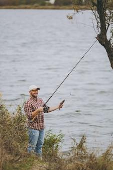 Młody nieogolony uśmiechnięty mężczyzna w kraciastej koszuli, czapce i okularach przeciwsłonecznych wyciągnął wędkę i trzyma złowioną rybę na brzegu jeziora w pobliżu krzewów i trzcin. styl życia, rekreacja, koncepcja wypoczynku rybaka