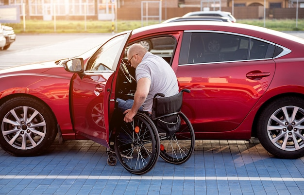 Młody niepełnosprawny kierowca wsiadający do czerwonego samochodu z wózka inwalidzkiego