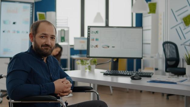 Młody niepełnosprawny kierownik projektu patrzący z przodu uśmiechnięty siedzący na wózku inwalidzkim w pokoju biurowym, pracujący nad projektem finansowym z zespołem