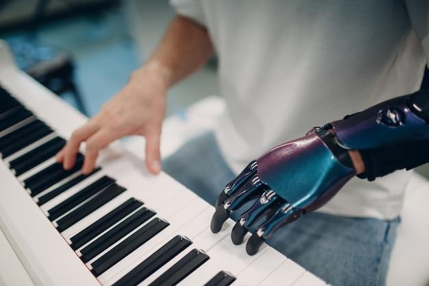 Młody niepełnosprawny mężczyzna grający na fortepianie elektronicznym syntezatorze ze sztuczną protezą ręki w muzyce ...