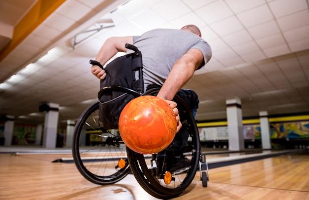 Młody niepełnosprawny mężczyzna na wózku inwalidzkim grający w kręgle w klubie