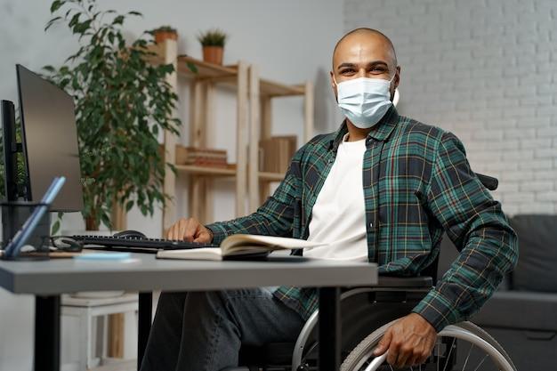 Młody niepełnosprawny mężczyzna na wózku inwalidzkim siedzący przy swoim stole roboczym w masce na twarz