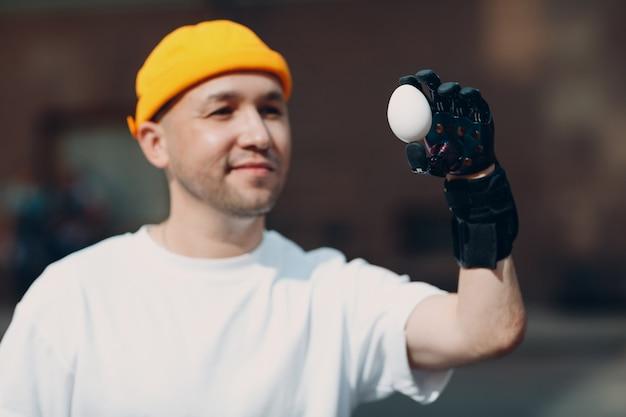 Młody niepełnosprawny mężczyzna trzyma kruche jajo kurze ze sztuczną protezą dłoni w zwykłych ubraniach