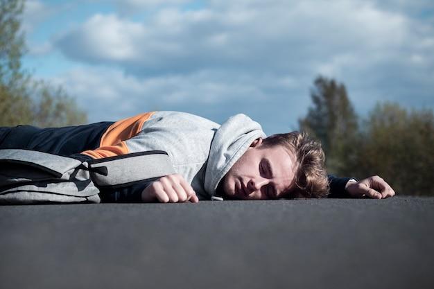 Młody nieprzytomny trup na miejscu wypadku, katastrofa na drodze. pieszy facet, nastolatek potrącony przez samochód na drodze podczas przekraczania autostrady. powalony mężczyzna leży na asfalcie. niebezpieczna sytuacja