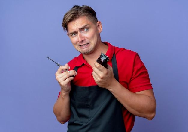 Młody niespokojny blond męski fryzjer w mundurze trzyma nożyczki i maszynkę do strzyżenia włosów na białym tle na fioletowej przestrzeni z miejsca na kopię