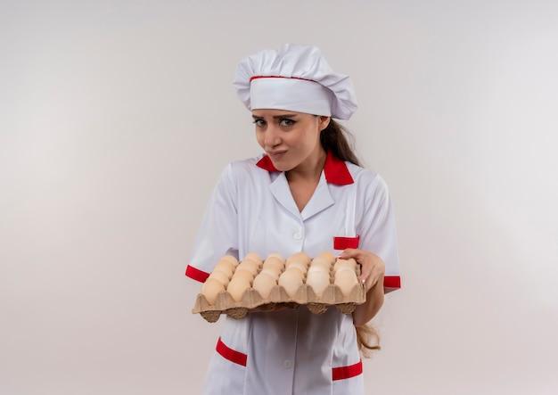Młody niespokojny kaukaski dziewczyna kucharz w mundurze szefa kuchni trzyma partię jaj i patrzy na aparat na białym tle z miejsca na kopię
