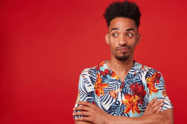 Młody nieszczęśliwy afroamerykanin ubrany w hawajską koszulę, patrząc w lewo w miejsce na kopię, stoi na czerwonym tle ze skrzyżowanymi rękami.