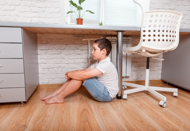 Młody nieszczęśliwy preteen smutny chłopiec w domu. cyberprzemoc, problemy nastolatków