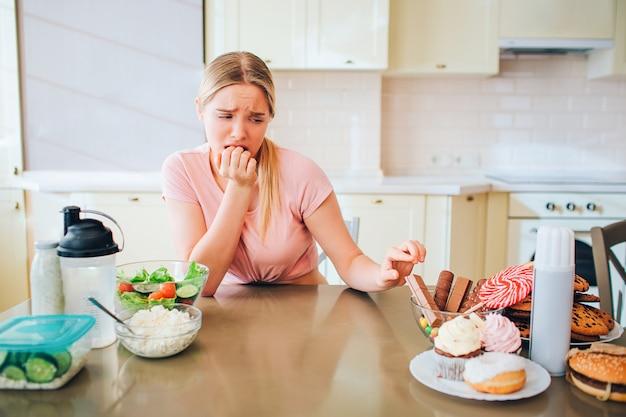 Młody niezadowolony szczupły model dotykając ciasteczka na stole w kuchni