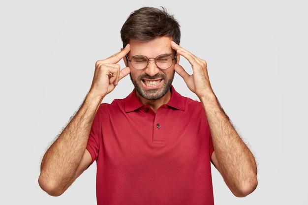 Młody niezadowolony zmęczony mężczyzna trzyma ręce na skroniach, potrzebuje regeneracji energii po nieprzespanej nocy, cierpi na ból głowy, ubrany w czerwoną koszulkę, ma zdenerwowany wygląd, zaciska zęby, stoi w domu