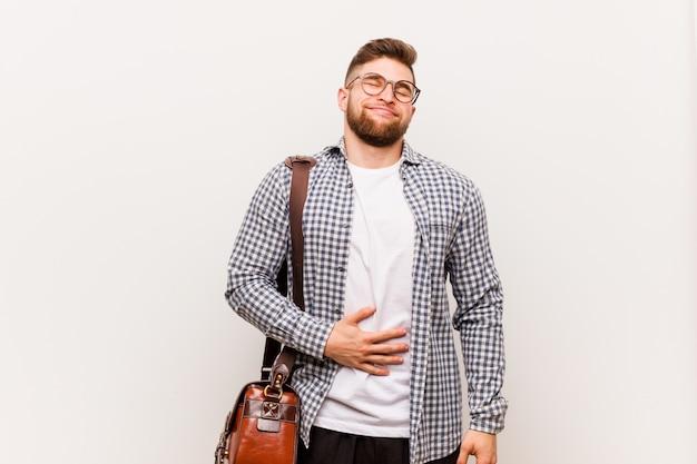 Młody nowoczesny biznesmen dotyka brzucha, uśmiecha się delikatnie, jedzenie i koncepcja satysfakcji.