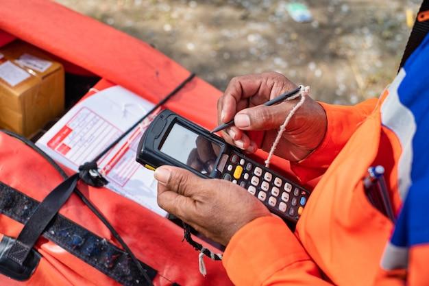 Młody nowoczesny człowiek dostawy używać skanera kodów kreskowych na czas pracy dostawy.