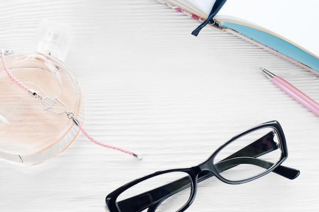 Młody nowoczesny kobieta w miejscu pracy. okulary, perfumy, długopis i notatnik na białym drewnianym stole, lato
