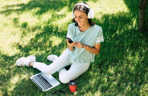 Młody nowoczesny piękny szczęśliwy pewna siebie kobieta w słuchawkach ze smartfonem pracuje na laptopie siedząc na trawniku.