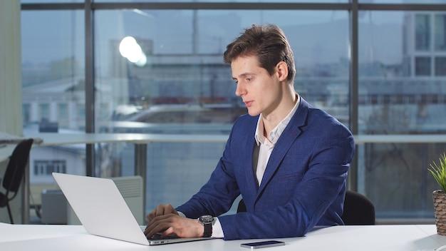 Młody nowożytny biznesmen pracuje przy biurkiem w biurowym używa laptopie