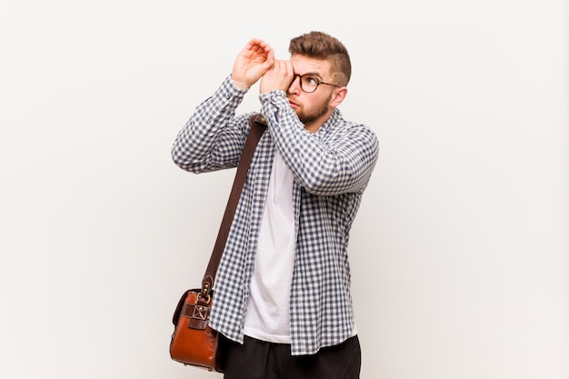 Młody nowożytny biznesowy mężczyzna patrzeje daleki utrzymujący on rękę na czole.
