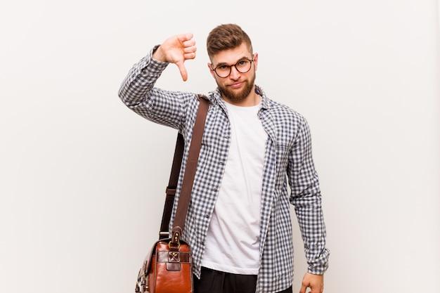Młody nowożytny biznesowy mężczyzna pokazuje niechęć gest, kciuk w dół