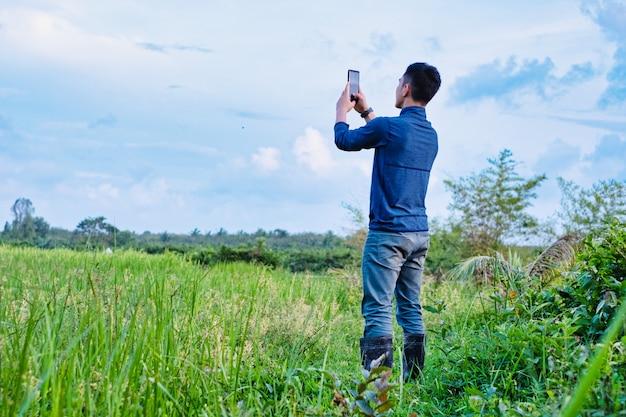 Młody nowożytny rolnik używa telefon komórkowy technologię w rolniczym polu.