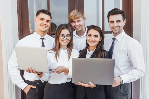 Młody obiecujący biznes zespół dziewcząt i chłopców w biznesowym wizerunku z laptopami w rękach.