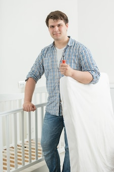 Młody oczekujący ojciec wkłada materac do łóżeczka dziecka