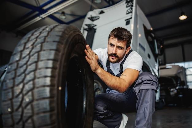 Młody oddany, ciężko pracujący mechanik kucający w garażu firmy importowo-eksportowej i przygotowujący się do zmiany opony w ciężarówce.