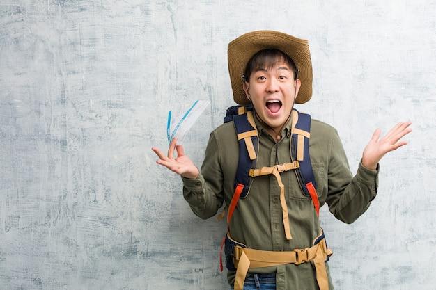 Młody odkrywca chińczyk posiadający bilety lotnicze świętujący zwycięstwo lub sukces