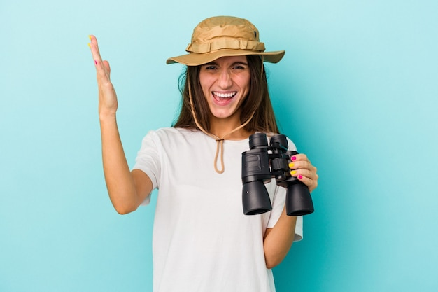 Młody odkrywca kaukaski kobieta trzyma lornetkę na białym tle na niebieskim tle odbiera miłą niespodziankę, podekscytowany i podnosząc ręce.