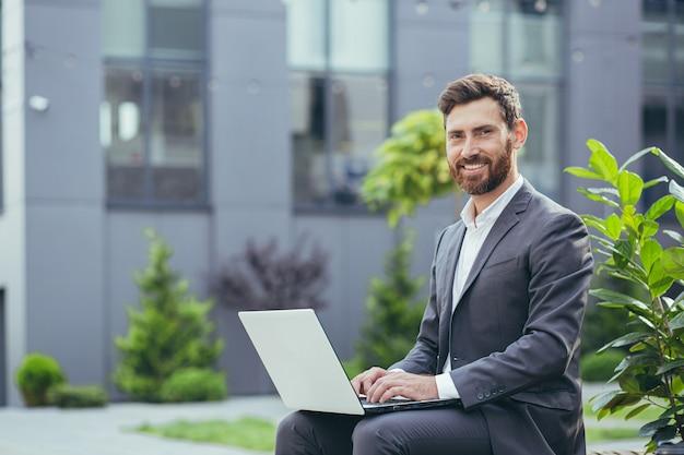 Młody, odnoszący sukcesy biznesmen pracujący na laptopie, brodaty mężczyzna w garniturze patrzy na kamerę i uśmiecha się, w pobliżu nowoczesnego centrum biurowego na zewnątrz