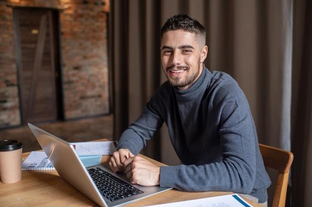 Młody, odnoszący sukcesy biznesmen z laptopem, patrzący na ciebie
