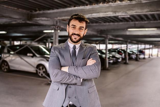 Młody, odnoszący sukcesy, brodaty dealer samochodowy w garniturze, stojący na parkingu z rękami skrzyżowanymi