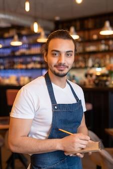 Młody, odnoszący sukcesy kelner w fartuchu, robiąc notatki w notatniku, przyjmując zamówienia klienta podczas pracy w kawiarni lub restauracji